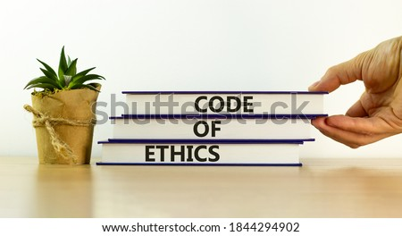 Books with text 'code of ethics' on beautiful wooden table, white background. Male hand and house plant. Business concept. Copy space. Stock photo ©