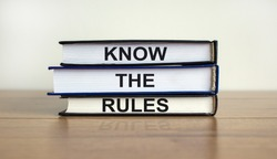 Books with text 'know the rules' on beautiful wooden table. White background. Business concept. Copy space.