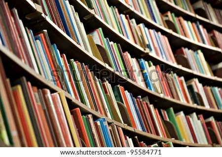 Bookshelf in library with many books. Shallow dof.