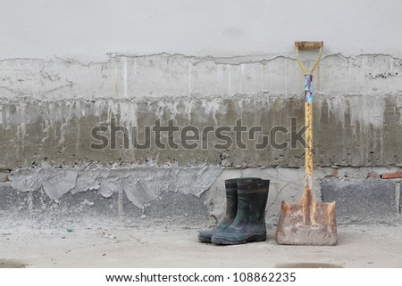 boot and showel on construction wall.