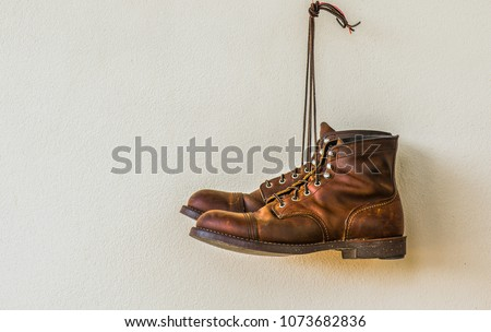 boot shoe hangs on  wooden wall