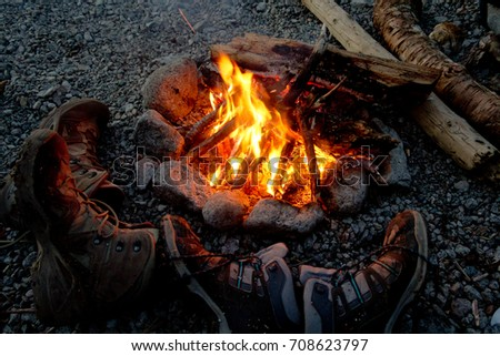 Boots drying near the bonfire during the hike #708623797