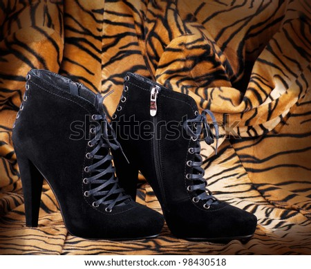 Boots from suede against a skin of a tiger