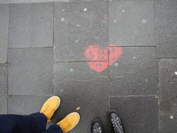 boots next to red heart drawn on pavement