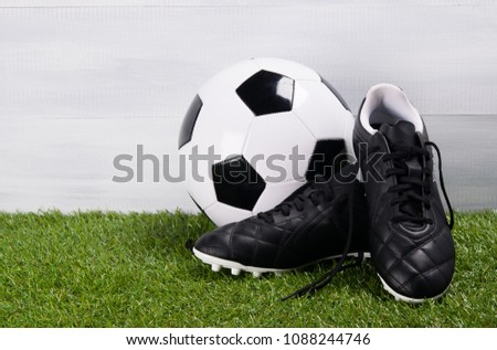 87cc8412f boots, soccer ball, on the grass, on a gray background #1088244746