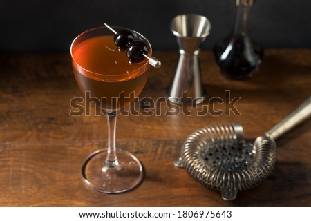 Boozy Rob Roy Cocktail with Scotch and a Cherry Garnish Foto stock ©