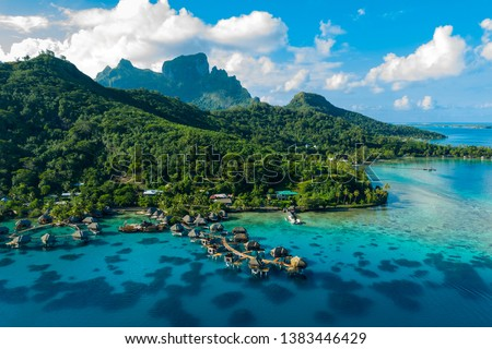 Bora Bora aerial drone video of travel vacation paradise with overwater bungalows luxury resort, coral reef lagoon ocean beach. Mount Otemanu, Bora Bora, French Polynesia, Tahiti, South Pacific Ocean #1383446429
