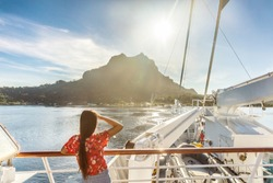 Bora bora island luxury cruise ship travel tourist woman watching sunset on balcony deck of Europe mediterranean cruising destination. Summer vacation cruiseship sailing away on holiday.