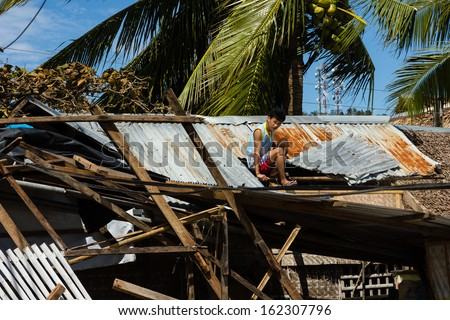 BORACAY, PHILIPPINES - NOVEMBER 9 2013:  A Flilippino man attempts to repair the roof of his typhoon ruined building.  Super Typhoon Haiyan is one of the biggest recorded storms to ever hit land