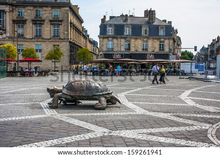 BORDEAUX, FRANCE - JULY 14: People walk on the Place de la Victoire near the famous sculpture Turtle with grapes in Bordeaux, France on July 14, 2013.