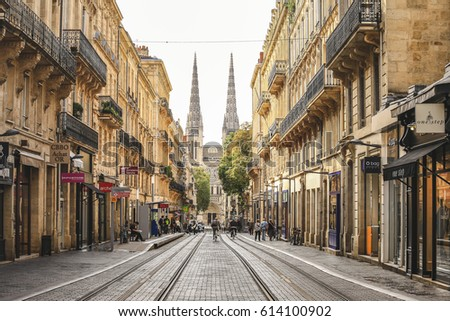 BORDEAUX, FRANCE - SEPTEMBER 30, 2016 : City street scene with tram rails and Saint Andre Cathedral on the back in Bordeaux, France #614100902