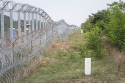 Border fence between Subotica (Serbia) & Kelebia (Hungary) with boundary marker. This border wall was built to stop the incoming refugees & migrants during the refugees crisis, on Balkans Route.