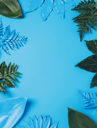 Border frame with fresh palm leaves on blue background. Minimal product showcase or template concept with copy space. Summer tropical layout. Flat lay, top view.