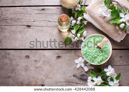 Border from spa products.  Sea salt in bowl, towels, aroma oil in bottles and flowers on  vintage  wooden background. Selective focus. Flat lay with copy space.
