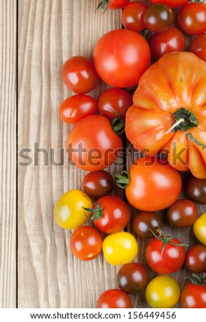 Border made from yellow, red and black tomatoes on wooden background