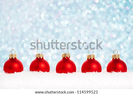 Border of Christmas tree decorations in snow against lights background