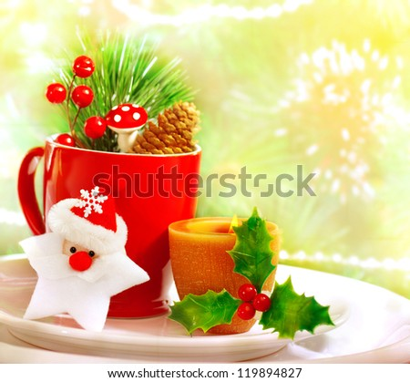Border of Christmastime utensil set, red tea cup standing on white plate and decorated with Santa Clause star toy, yellow candle, twig of berry, fir cone and branch of Christmas tree, holiday dinner