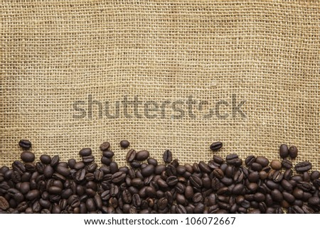 Border of coffee beans over burlap sack background.  Lots of copy space.