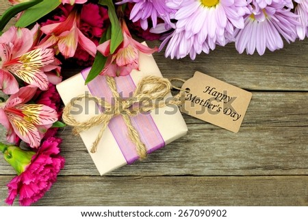 Border of flowers with Mother\'s Day gift box and tag against a rustic wood background