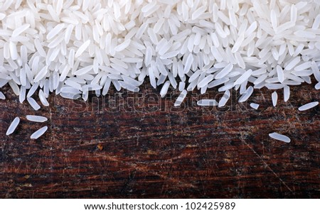 Border of long grain white rice on wood background