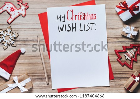 Border of pine tree toys with blank piece of paper and pencil to write x-mas wish list. Holiday concept. Christmas composition.