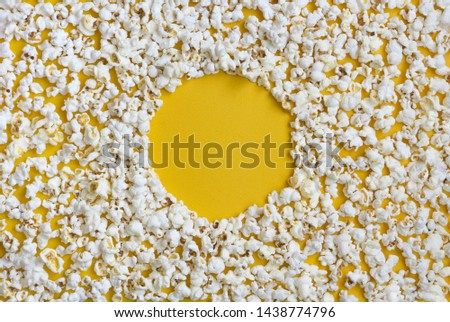 Border of popcorn scattered over yellow background with copy space, top view. Minimalistic design for movie poster, entertainment concept. Popcorn pattern on yellow.