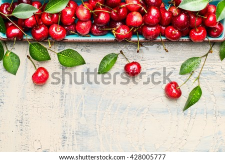 Border of sweet cherries with green leaves on light wooden background, top view, place for text. Summer fruits and berries concept.