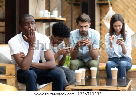 Bored African American man sitting with people with phone dependence, yawning, friends using mobile devices, apps, looking at screen, ignore each other in cafe, smartphone addiction concept