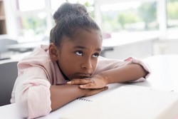bored african american schoolgirl sitting at desk with head on hands during lesson