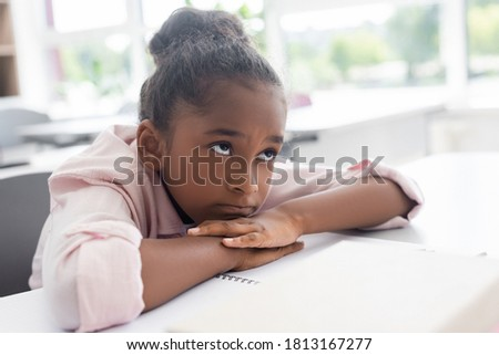 bored african american schoolgirl sitting at desk with head on hands during lesson Foto d'archivio ©