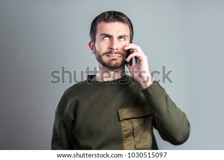 Bored and frustrated man having a dull conversation over his cell phone Сток-фото ©