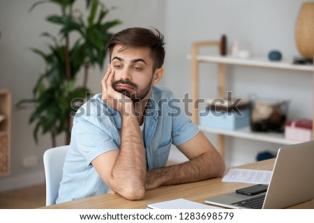 Bored at work concept, tired unmotivated male worker wasting time at workplace distracted from boring job, lazy man disinterested in dull monotonous routine feeling lack of ideas thinking of boredom