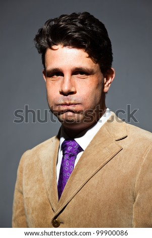 Bored business man with light brown suit and purple tie isolated on dark background. Studio portrait.