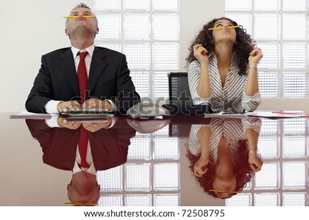 Bored businessman and secretary playing with pencil and having fun in office meeting room. Horizontal shape, front view, waist up