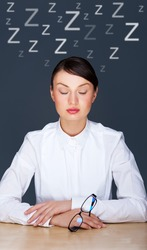 Bored businesspeople: woman sitting at desk with closed eyes. Young  caucasian business woman at her office.