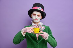Bored displeased man hatter obsessed with drinking tea wears big hat green costume bowtie poses against purple background comes on spooky party celebrates halloween stands indoor. Fictional character
