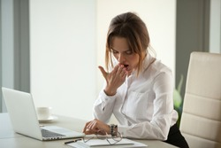 Bored drowsy businesswoman yawning looking at wristwatch checking time tired of tedious monotonous overwork, impatient lazy employee office worker waiting for dull day finish working overtime concept