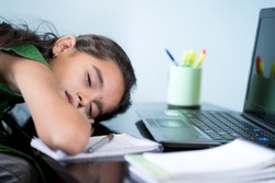 Bored Girl child slept infront of laptop - concept of kid tired from e-learning or online education at home during covid-19 or coronavirus outbreak