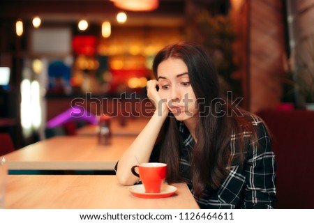 Bored Girl Waiting for her Date in a Coffee Shop. Stood up woman having a bad time alone in the restaurant