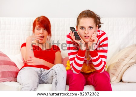 Bored girl yawning while her girlfriend attentively watching TV  at living room