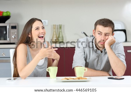 Bored husband hearing his wife talking during breakfast in the kitchen at home