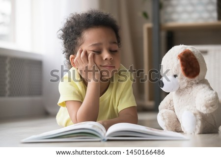 Bored little biracial boy lie on warm floor at home reading book together with stuffed teddy toy, funny black preschooler child distracted from studying dream playing with plush friend in living room