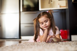 Bored little girl looking at tablet. Loneliness childhood.