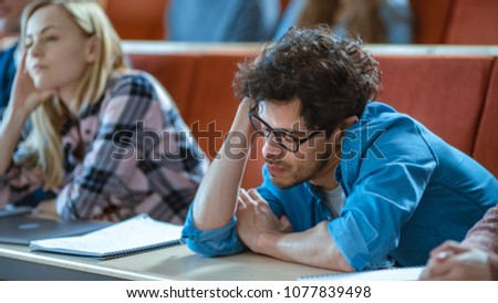 Bored Male Student Listens Lecture at the University. Tired, Exhausted and Overworked Young Male Holds His Head. #1077839498