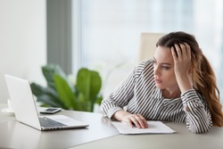 Bored millennial female worker lie at office desk look at laptop screen think about problem solution, unmotivated businesswoman search inspiration, tired of monotonous work. Lack of motivation concept