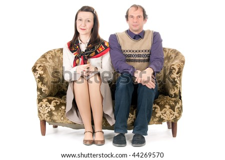 bored  old looking couple sitting on vintage couch isolated on white