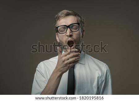 Bored overworked man yawning and feeling tired, he is covering his mouth with his hand, laziness and insomnia concept Foto d'archivio ©