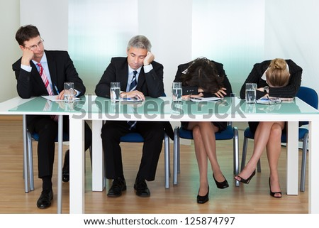 Bored panel of professional judges or corporate interviewers lounging around on a table napping as they wait for something to happen Сток-фото ©