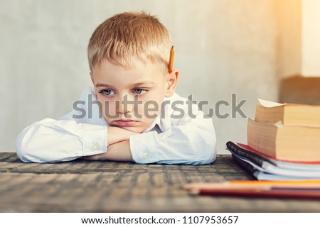 Bored pupil. Tired bored little boy sitting sadly at the table with books by his side
