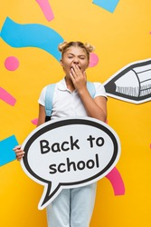 bored schoolgirl yawning while holding speech bubble with back to school lettering near paper pencil and colorful elements on yellow